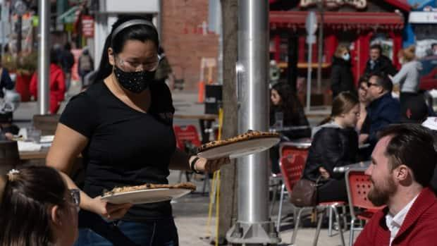 A server wearing a mask brings meals to two people sitting on a patio in Ottawa's ByWard Market on March 20, 2021.
