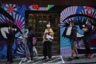 People wearing face masks to help curb the spread of the coronavirus wait outside a bakery in Hong Kong, Monday, Nov. 30, 2020. (AP Photo/Kin Cheung)