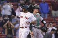 Boston Red Sox's Xander Bogaerts, left, celebrates as he arrives at home plate after hitting a two-run home run as Oakland Athletics' Sean Murphy, right, looks on in the first inning of a baseball game, Thursday, May 13, 2021, in Boston. (AP Photo/Steven Senne)