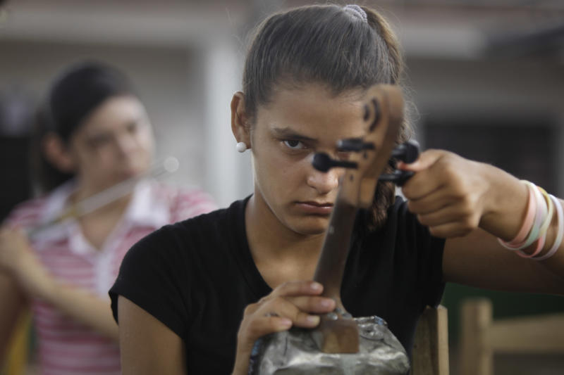 "In this Dec. 11, 2012 photo, Tania Vera, 15, tunes her violin during a practice session with ""The Orchestra of Instruments Recycled From Cateura"" in Cateura, a vast landfill outside Paraguay's capital of Asuncion, Paraguay. I never thought my dreams would become reality,"" said Vera, who lives in a wooden shack by a contaminated stream. Her mother has health problems, her father abandoned them, and her older sister left the orchestra after becoming pregnant. Tania, though, keeps to her goal of becoming a veterinarian as she keeps up with the music. (AP Photo/Jorge Saenz)"