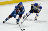 Colorado Avalanche defenseman Ryan Graves, left, reaches out to pick up the puck as St. Louis Blues center Brayden Schenn defends in the first period of an NHL hockey game Friday, Jan. 15, 2021, in Denver. (AP Photo/David Zalubowski)