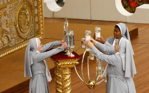 Nuns place on the altar the relics of five new saints during an open-air canonization ceremony led by Pope Benedict XVI, in St. Peter's Square at the Vatican, in 2009. - Credit: AP