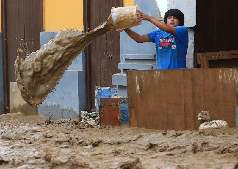 A local resident bails water from behind a barrier as a flash flood hits the city of Trujillo, 570 kilometres north of Lima on March 18, 2017 (AFP Photo/CELSO ROLDAN)