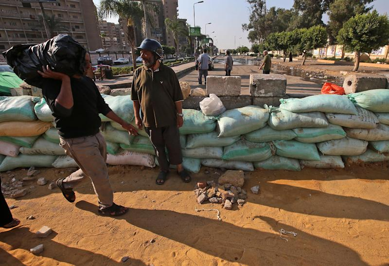 An Egyptian man, left, carries a plastic bag as he passes a supporter of Egypt's ousted President Mohammed Morsi standing by sand barriers recently set up where protesters have installed their camp at Nasr City in Cairo, Egypt, Thursday, July 18, 2013. Pro-Morsi protesters continued their sit-in in front of the Rabaah al-Adawiya mosque in Cairo for the third week. Residents of the area have complained blocking the roads and using nearby gardens for washing and sewage purposes. Since Morsi was toppled by the military in the most recent uprising, protesters vowed to remain on the streets till he is back to presidency and called the transition a coup. (AP Photo/Hussein Malla)