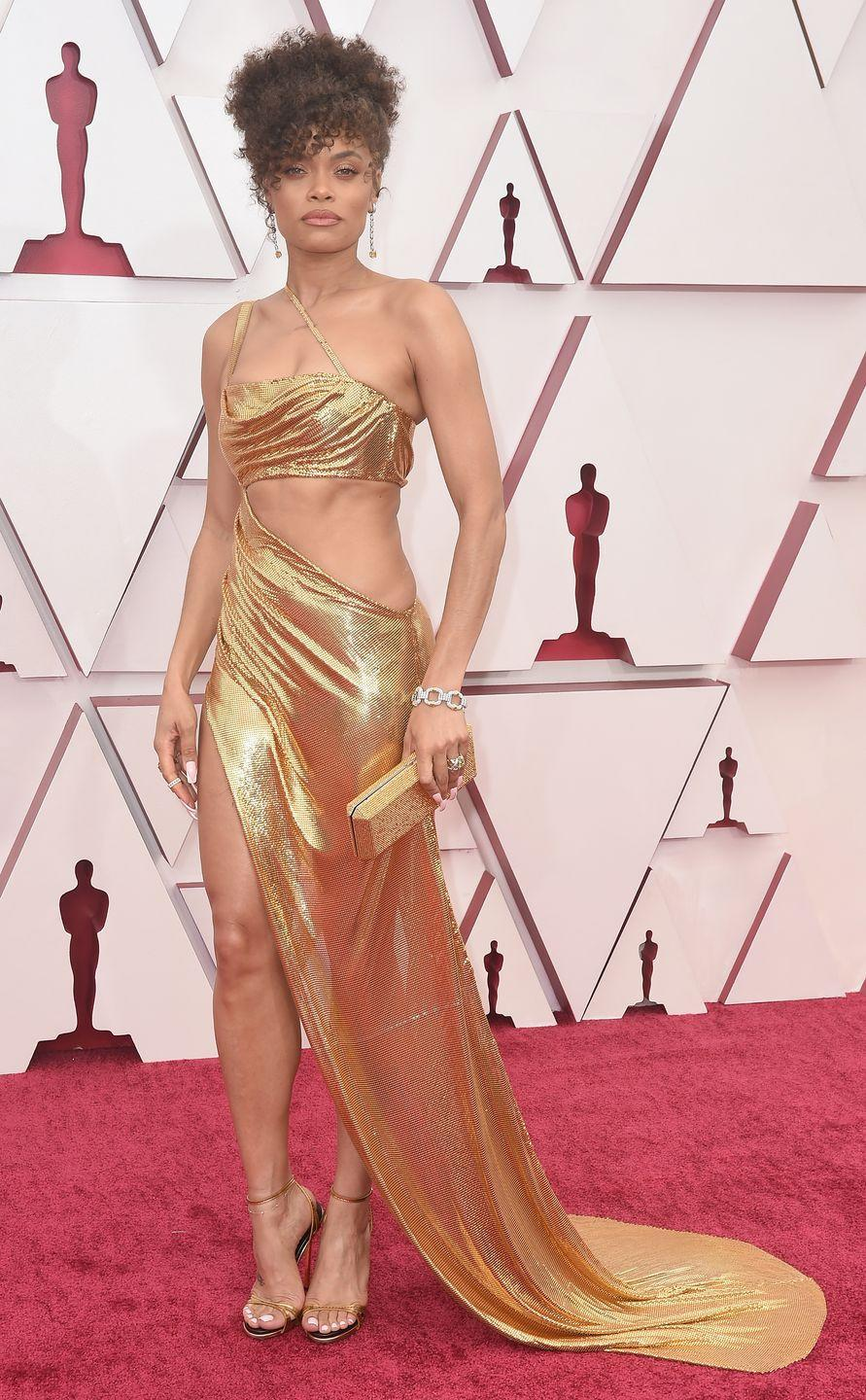 """<p>Andra Day has had quite the introductory award season on the red carpet with the actress pulling out all the stops throughout, and, she may have saved her best look for last. The star wore a very slinky gold gown by Vera Wang for the occasion, which she teamed with strappy heels and statement earrings by Tiffany & Co, a look which her <a href=""""https://www.instagram.com/p/COHTDvxlpFA/"""" rel=""""nofollow noopener"""" target=""""_blank"""" data-ylk=""""slk:stylist Wouri Vice said was inspired by Cher."""" class=""""link rapid-noclick-resp"""">stylist Wouri Vice said was inspired by Cher.</a></p>"""
