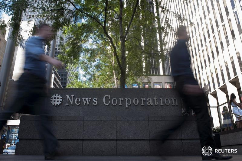 Passers-by walk near the News Corporation building in New York