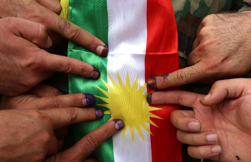 Members of a Kurdish peshmerga battalion show their ink-stained fingers in front of a Kurdish flag after voting in the Kurdish independence referendum on September in defiance of the federal government in Baghdad (AFP Photo/SAFIN HAMED)