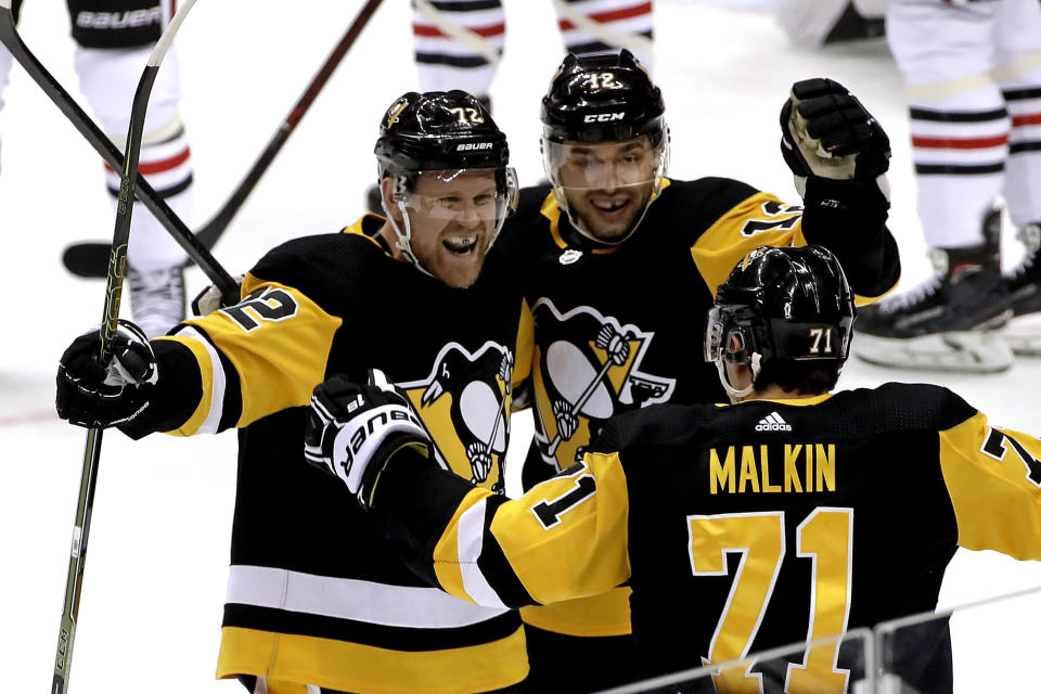 Pittsburgh Penguins' Patric Hornqvist (72) celebrates his goal with Dominik Simon (12) and Evgeni Malkin (71) during the first period of an NHL hockey game against the Chicago Blackhawks in Pittsburgh, Sunday, Jan. 6, 2019. (AP Photo/Gene J. Puskar)