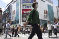 People walk across a crossing near Shimbashi Station in Tokyo Thursday, July 29, 2021, a day after the record-high coronavirus cases were found in the Olympics host city. (AP Photo/Kantaro Komiya)