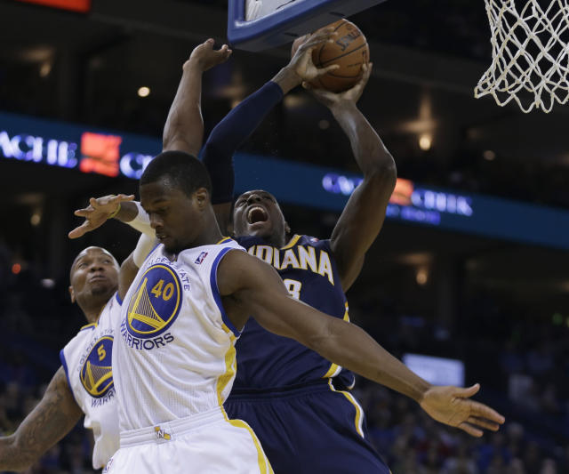 Indiana Pacers' Ian Mahinmi shoots over Golden State Warriors' Harrison Barnes (40) and Marreese Speights (5) during the second half of an NBA basketball game Monday, Jan. 20, 2014, in Oakland, Calif. (AP Photo/Ben Margot)