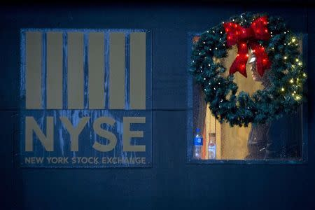 A police officer is pictured though a wreath as he stands guard in the rain at the New York Stock Exchange on the last day of trading before Christmas in the Manhattan borough of New York, December 24, 2014. REUTERS/Carlo Allegri