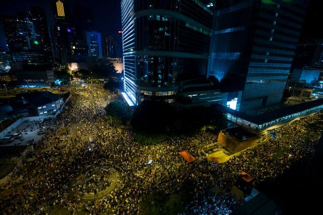 Thousands of protesters attend a rally outside the government headquarters in Hong Kong as riot police stand guard September 27, 2014.