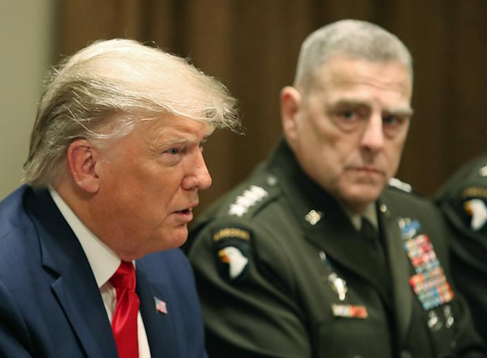 Former President Donald Trump speaks at the White House, as the chairman of the joint chiefs of staff, Army Gen. Mark Milley, looks on in October 2019.