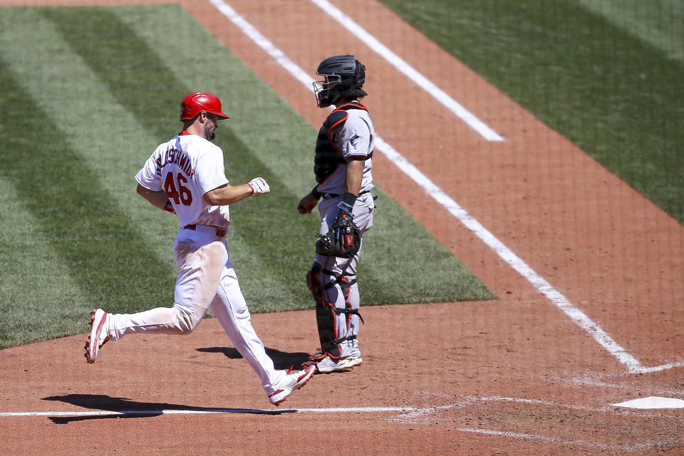 St. Louis Cardinals' Paul Goldschmidt, left, scores a run as Miami Marlins catcher Jorge Alfaro, right, looks on during the ninth inning of a baseball game Wednesday, June 16, 2021, in St. Louis. (AP Photo/Scott Kane)