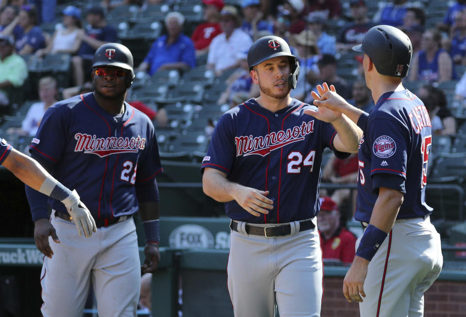 Minnesota Twins Miguel Sano (22), C.J. Cron (24) and Jason Castro (15) celebrate after scoring on a triple by Jorge Polanco in the eighth inning of a baseball game against the Texas Rangers, Sunday, Aug. 18, 2019, in Arlington, Texas. (AP Photo/Richard W. Rodriguez)