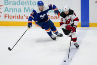 New York Islanders' Ross Johnston (32) defends against New Jersey Devils' Connor Carrick (5) during the first period of an NHL hockey game Thursday, May 6, 2021, in Uniondale, N.Y. (AP Photo/Frank Franklin II)