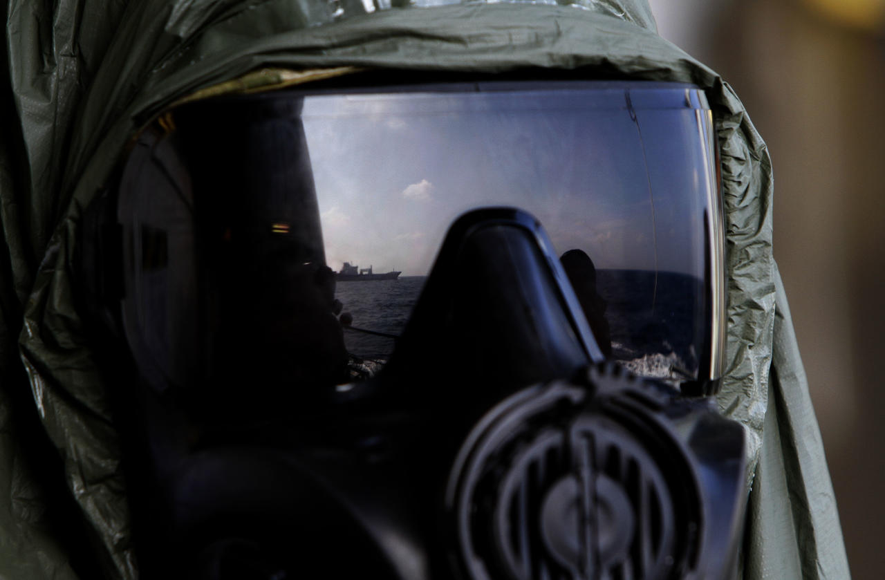A crew member of the Danish warship Esbern Snare wears a protective mask which shows the reflection of the Danish cargo ship Ark Futura, during emergency drills on the sea between Cyprus and Syria, Sunday, Jan. 5, 2014. Two cargo ships and their warship escorts set sail at waters near Syria where they will wait for orders on when they can head to the Syrian port of Latakia to pick up more than 1,000 tons of chemical agents. (AP Photo/Petros Karadjias)