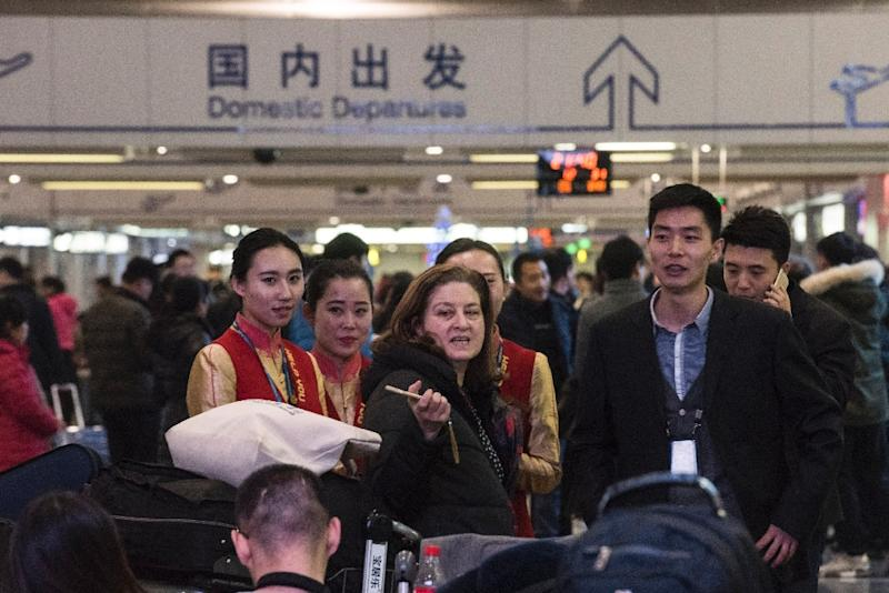Ursula Gauthier (L), the Beijing-based correspondent for French news magazine L'Obs, speakes with hostesses at the airport before she takes her flight back to France, in Beijing on December 31, 2015