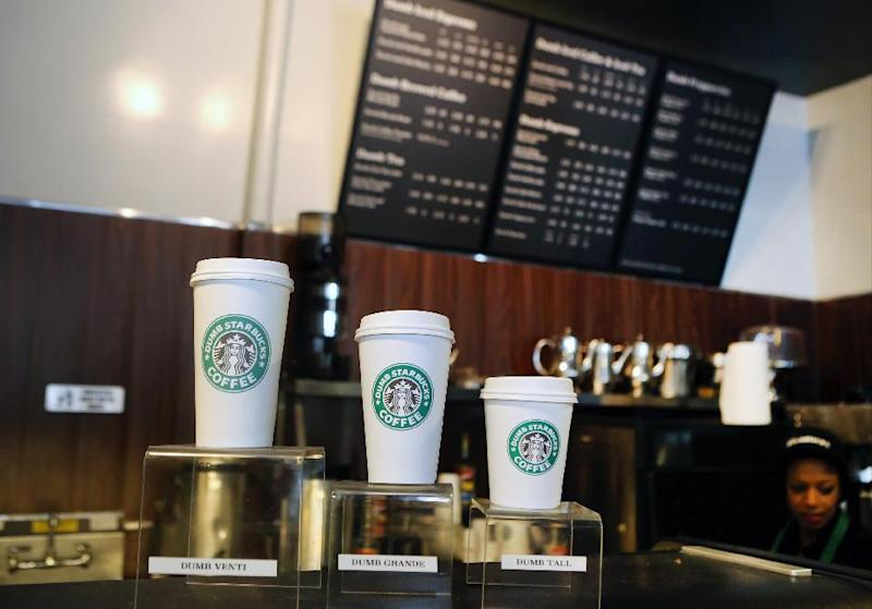 "Featured coffee drinks sizes, Dumb Venti, Dumb Grande, and Dumb Tall are displayed inside the Dumb Starbucks in Los Angeles, Monday, Feb. 10, 2014. The mysterious shop named ""Dumb Starbucks"" is serving coffee in Los Angeles after drawing weekend crowds that waited in a line two blocks long. The line Monday was far shorter, however. The store resembles a Starbucks with a green awning and mermaid logo, but with the word ""Dumb"" attached above the Starbucks sign. (AP Photo/Damian Dovarganes)"