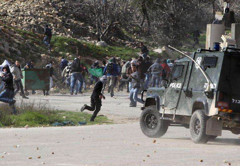 Palestinian protesters throw stones towards an Israeli police vehicle in front of Ofer prison, on February 15, 2013