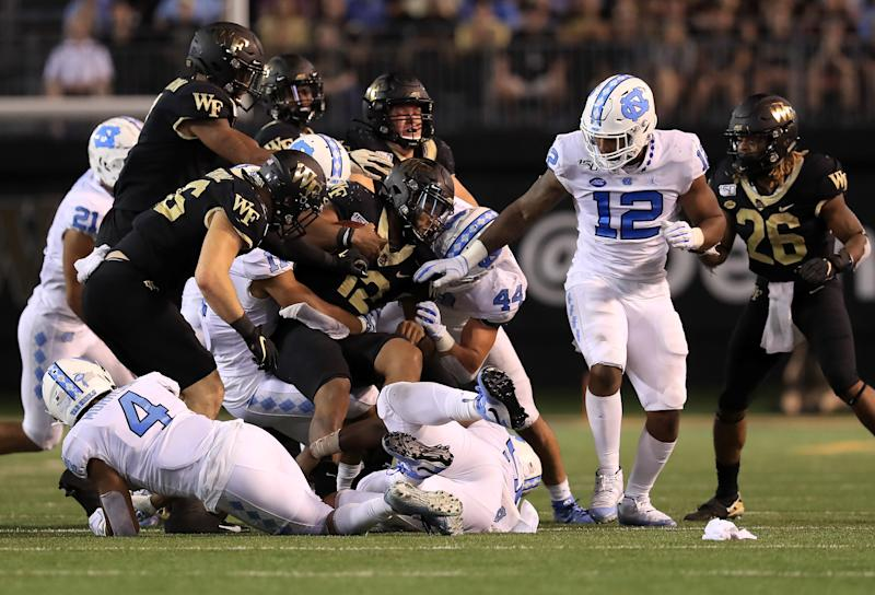 WINSTON SALEM, NORTH CAROLINA - SEPTEMBER 13: Jamie Newman #12 of the Wake Forest Demon Deacons is tackled by the defense of the North Carolina Tar Heels during their game at BB&T Field on September 13, 2019 in Winston Salem, North Carolina. (Photo by Streeter Lecka/Getty Images)