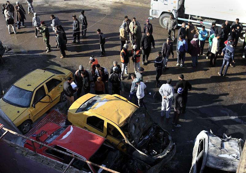 People gather at the scene of a car bomb attack in Hurriya neighborhood of Baghdad, Iraq, Thursday, Jan. 10, 2013. A car bomb explosion near a bus stop in the capital, have killed and wounded scores of people, police said. (AP Photo/Karim Kadim)
