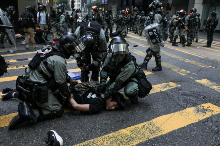 Police detain a man during a flash mob to block roads in Hong Kong's Central business district amid some of the worst violence in five months of unrest