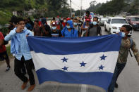 Migrants trying to reach the U.S. border walk along a highway in Choloma, Honduras, Thursday, Jan. 14, 2021. About 200 Honduran migrants, two holding a Honduran national flag, resumed walking toward the border with Guatemala early Thursday, a day before a migrant caravan was scheduled to depart San Pedro Sula. (AP Photo/Delmer Martinez)