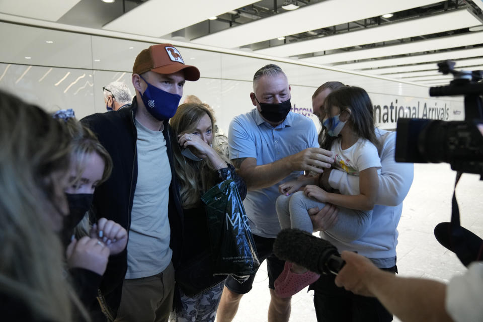 A reunited family are interviewed by the media after some of them arrived on a flight, at Terminal 5 of Heathrow Airport in London, Monday, Aug. 2, 2021. Travelers fully vaccinated against coronavirus from the United States and much of Europe were able to enter Britain without quarantining starting today, a move welcomed by Britain's ailing travel industry. (AP Photo/Matt Dunham)