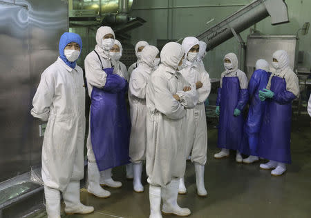 Employees stand during a seizure conducted at the Husi Food factory in Shanghai