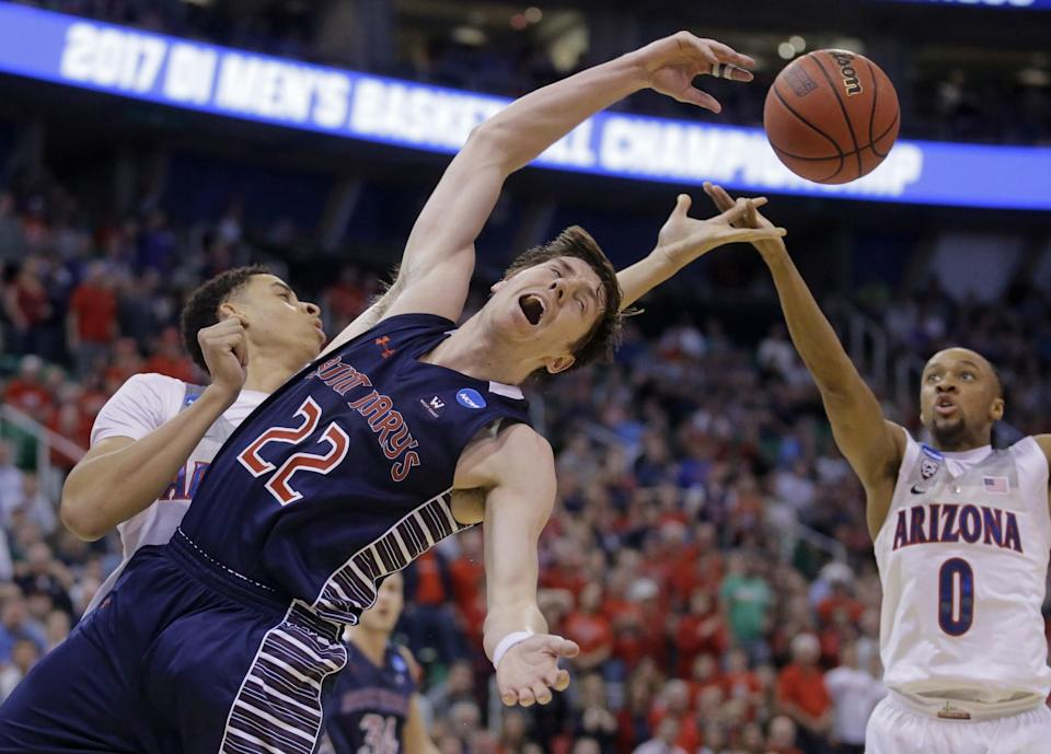 <p>Saint Mary's forward Dane Pineau (22) reaches for the ball as Arizona's Chance Comanche, rear, and Parker Jackson-Cartwright (0) defend during the second half of a second-round college basketball game in the men's NCAA Tournament Saturday, March 18, 2017, in Salt Lake City. Arizona won 69-60. (AP Photo/Rick Bowmer) </p>
