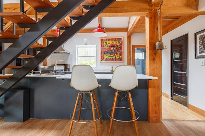"""A cabin that's equal parts rustic and polished, the post and beam converted barn is arranged in a traditional saltbox configuration that's completely devoid of nails (only joinery), which explains the impressive scale of the rugged rough-hewn timber posts. Another benefit of the old-school design? Plenty of space in the open floor plan that's decorated with Mid-Century icons, including Nogucci lighting. The exterior may be painted matte black, but the interiors are bright and airy with a flood of natural light courtesy of the floor-to-ceiling windows in the living area. But as is the case with most homes, the kitchen—a sizable gallery space lit by fire-engine-red Danish pendants—is the best room in the house. $349, Airbnb. <a href=""""https://www.airbnb.com/rooms/41459086?"""" rel=""""nofollow noopener"""" target=""""_blank"""" data-ylk=""""slk:Get it now!"""" class=""""link rapid-noclick-resp"""">Get it now!</a>"""