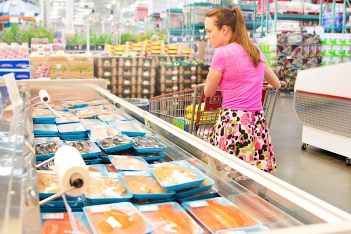 Woman Shopping for Fresh Fish Seafood in Supermarket Retail Store (Getty Images stock)