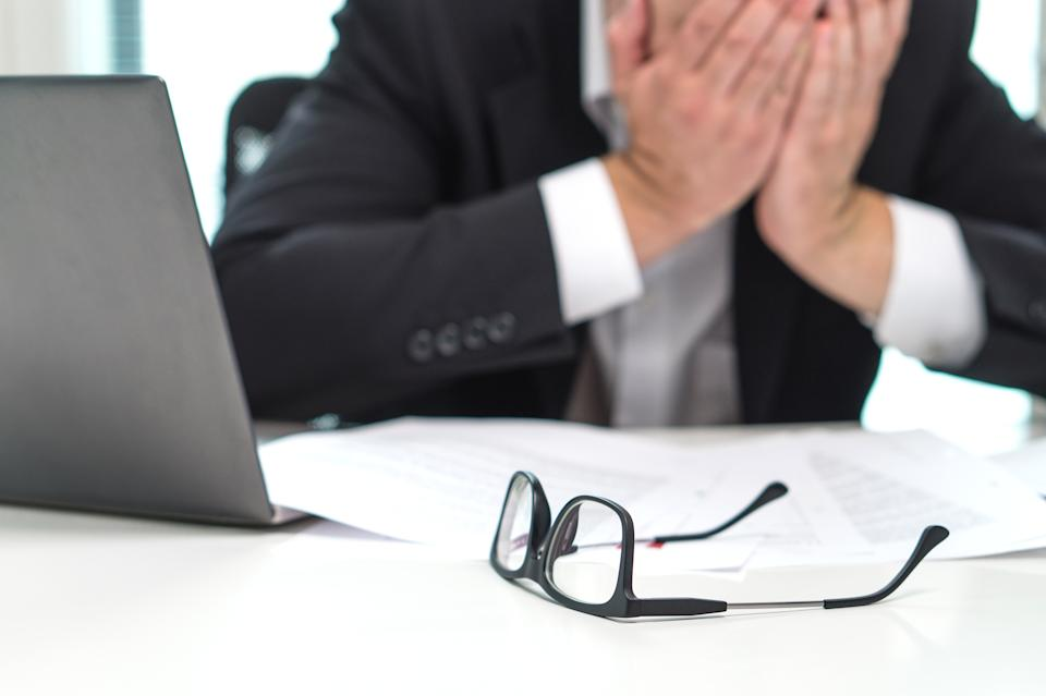 Stressed business man covering face with hands in office. Working over time or too much. Problem with failing business or confusion with crisis. Entrepreneur in bankruptcy.