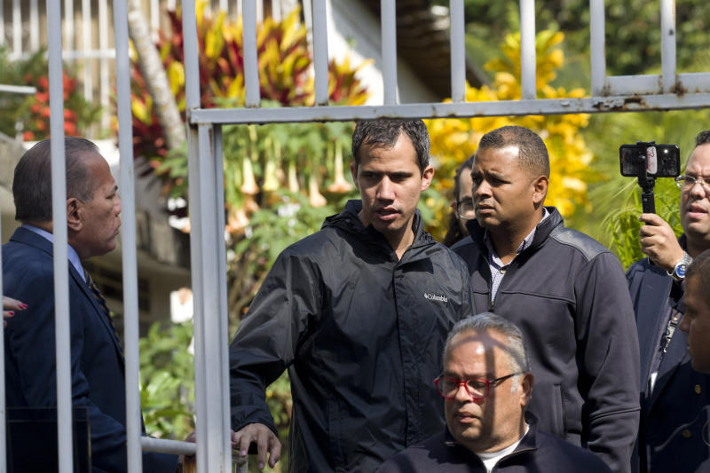 In this March 21, 2019 photo, Venezuelan opposition leader Juan Guaido stands near a gate at the home of top aide Roberto Marrero, in Caracas, Venezuela. Marrero was taken away by intelligence agents in an overnight operation on his home early Thursday. Guaido characterized the operation as a sign that Nicolas Maduro is losing his grip on power. (AP Photo/Ariana Cubillos)