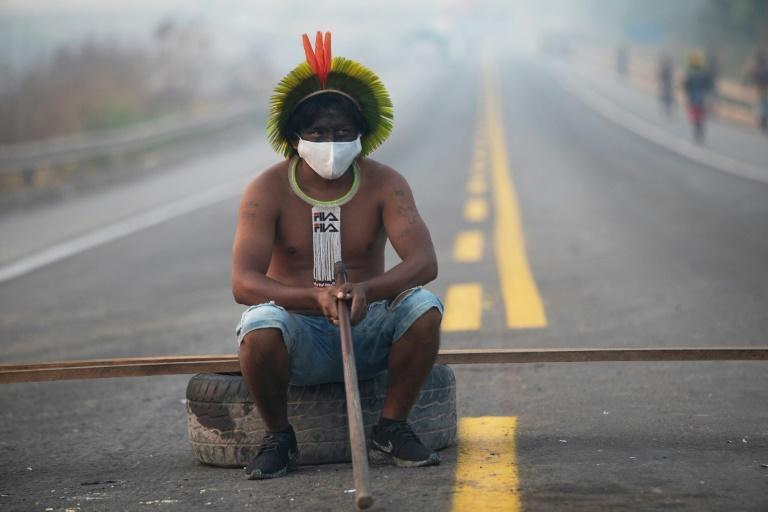 A member of the Kayapo tribe blocks a highway on the outskirts of Novo Progresso in Para State, Brazil, in August 2020 to protest illegal logging and mining in the rainforest and to seek action against Covid-19