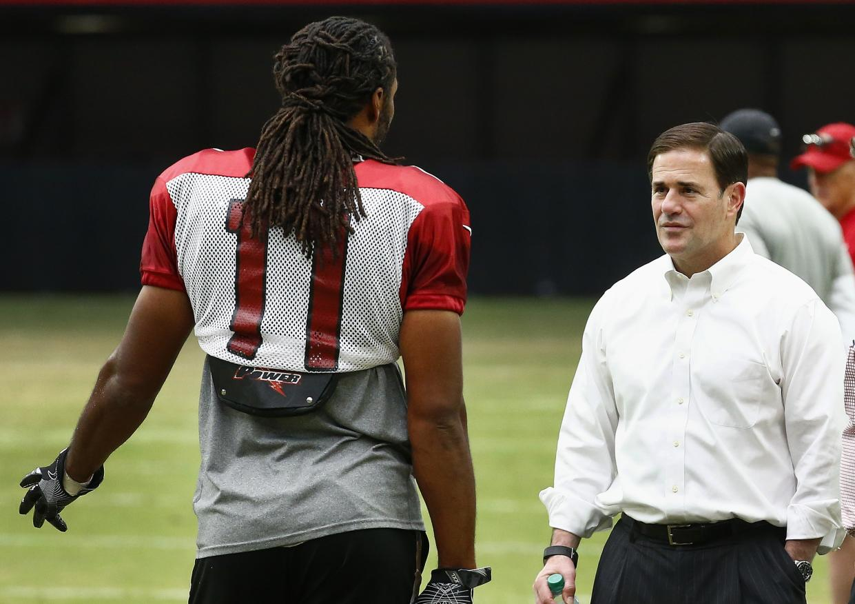 Arizona Cardinals wide receiver Larry Fitzgerald, left, talks with Republican Arizona Gov. Doug Ducey on the sideline during an NFL football training camp Wednesday, Aug. 23, 2017, in Glendale, Ariz. (AP Photo/Ross D. Franklin)