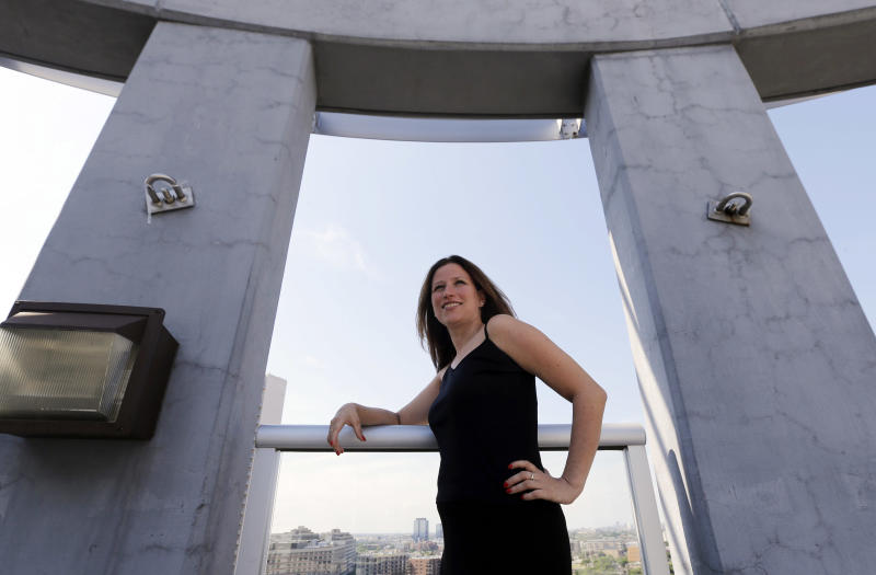 In this July 25, 2013 photo, Maura Duffy, 35, poses for a photo on the deck atop her apartment building in Chicago. Duffy, who was adopted at birth, is among 8,800 Illinois residents since 2010 who have been able to see their original birth certificates, because of a law that opened documents sealed for decades. Duffy met her birth mother for the first time last September and says she is thankful to her birth mother and adoptive family for all they did for her. (AP Photo/Nam Y. Huh)