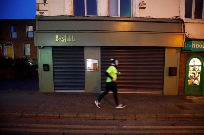 A runner jogs past the shuttered Bastible restaurant, after it closed its doors on Sunday amid the growing threat from the coronavirus disease (COVID-19), in Dublin, Ireland