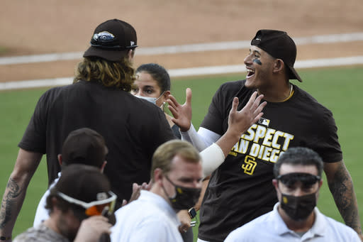 San Diego Padres' Chris Paddack, left, and Manny Machado celebrate after the Padres beat the Seattle Mariners 7-4 in a baseball game Sunday, Sept. 20, 2020, in San Diego. The Padres clinched a spot in the playoffs. (AP Photo/Denis Poroy)