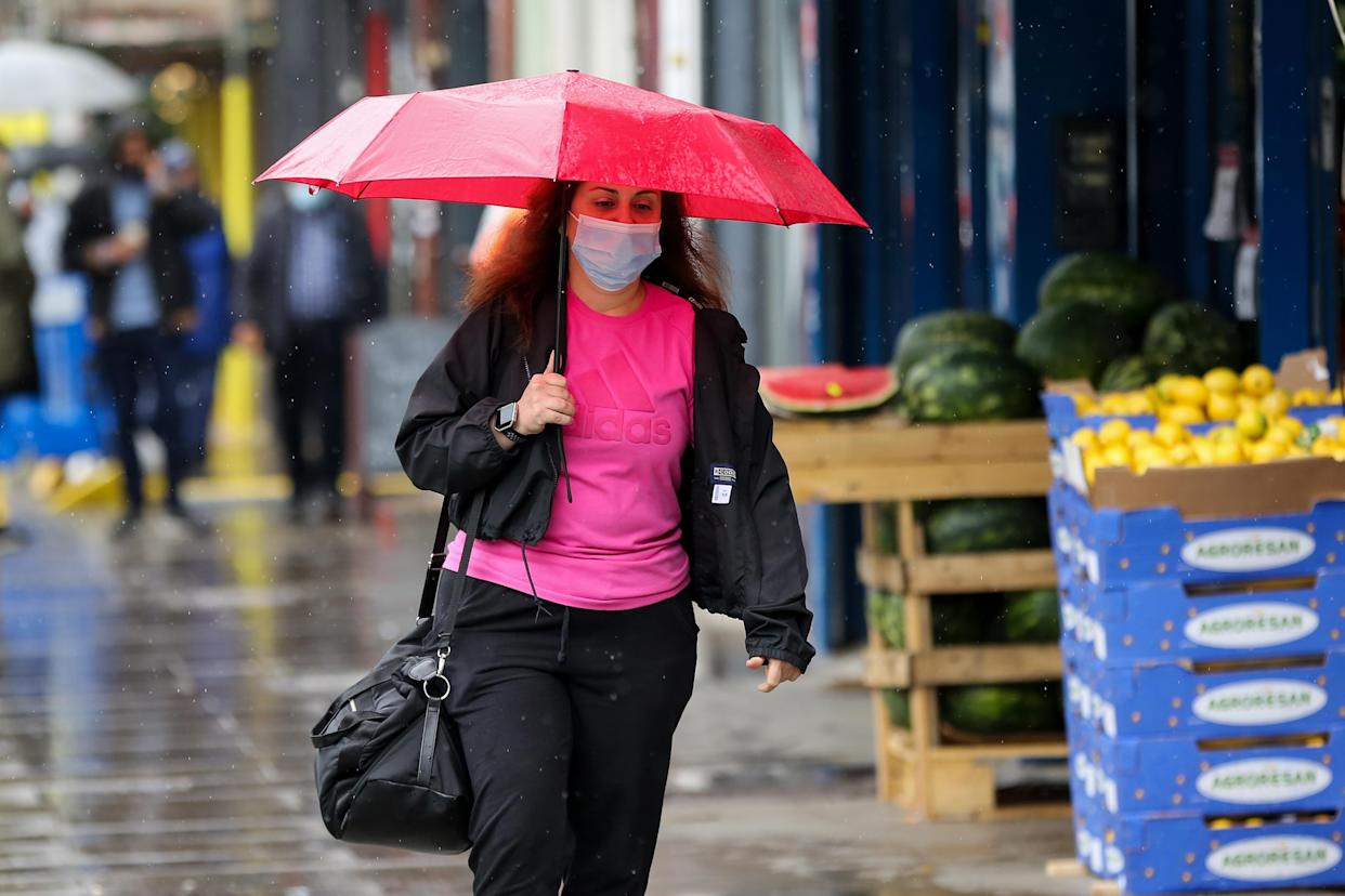 A woman shelters from rain beneath an umbrella in London. (Photo by Dinendra Haria / SOPA Images/Sipa USA)