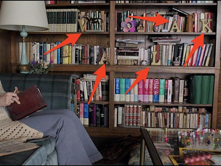 """Lorainne sitting in front of the bookshelf that spells out """"Valak"""" in """"The Conjuring 2"""""""
