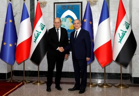 French Foreign Minister Jean-Yves Le Drian shakes hands with Iraqi Foreign Minister Mohamed Ali Alhakim at the Ministry of Foreign Affairs in Baghdad