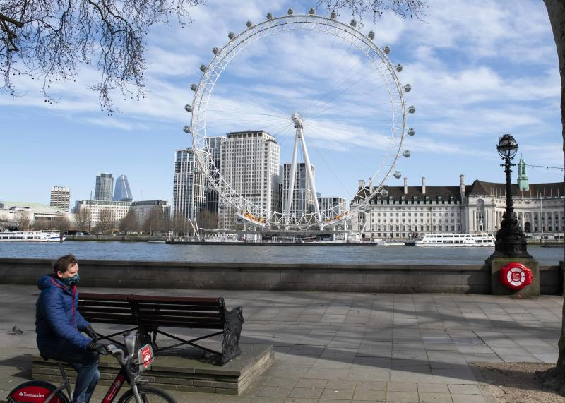 A member of the public wearing a protective mask cycles past an empty London Eye, during the Corona Virus outbreak, London. Picture date: Monday 23rd March 2020. Photo credit should read: David Jensen/ EMPICS Entertainment