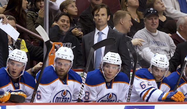 Edmonton Oilers coach Dallas Eakins, top, stands behind players, from left, Martin Marincin, Jesse Joensuu,Tyler Pitlick and Mark Arcobello during the first period of a preseason NHL hockey game against the Vancouver Canucks on Wednesday, Sept. 18, 2013, in Vancouver, British Columbia. (AP Photo/The Canadian Press, Darryl Dyck)