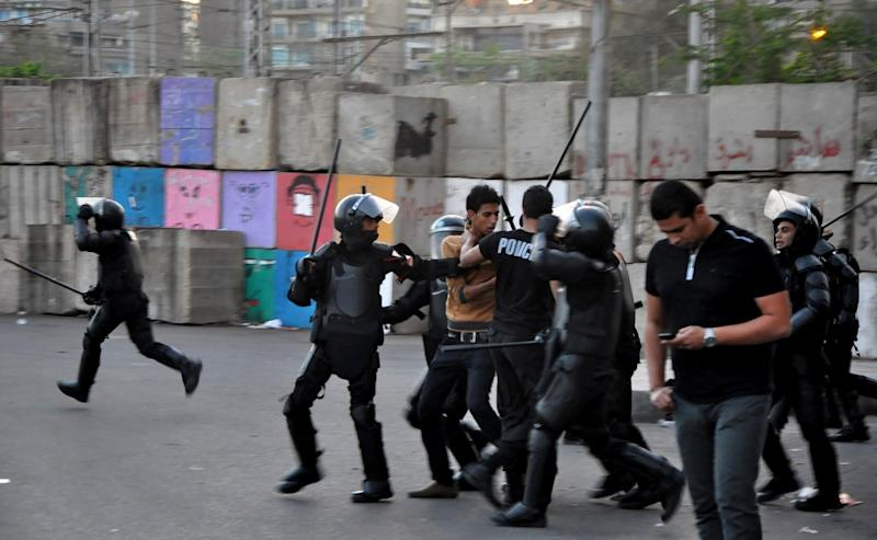 Egyptian riot police detain a protester during clashes outside the presidential palace in Cairo, Friday, April 26, 2013. Dozens of mostly masked protesters hurled stones and firebombs in clashes with riot police at Egypt's presidential palace in a Cairo suburb. Protests have become a weekly routine in Egypt, as the country has plunged in turmoil during most of the past two years since 2011 uprising which ousted longtime president Hosni Mubarak out of power. (AP Photo/Hussein Tallal)