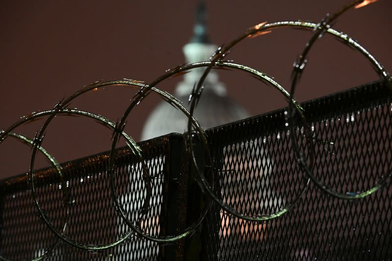 The U.S. Capitol is seen through barbed wire on a security fence after the Senate voted to acquit former U.S. President Donald Trump during his impeachment trial, in Washington