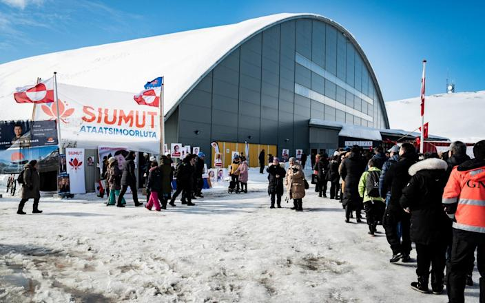 Voters stand in line during the parliamentary election, outside the Inussivik arena, in Nuuk, Greenland, April 6, 2021 - Reuters
