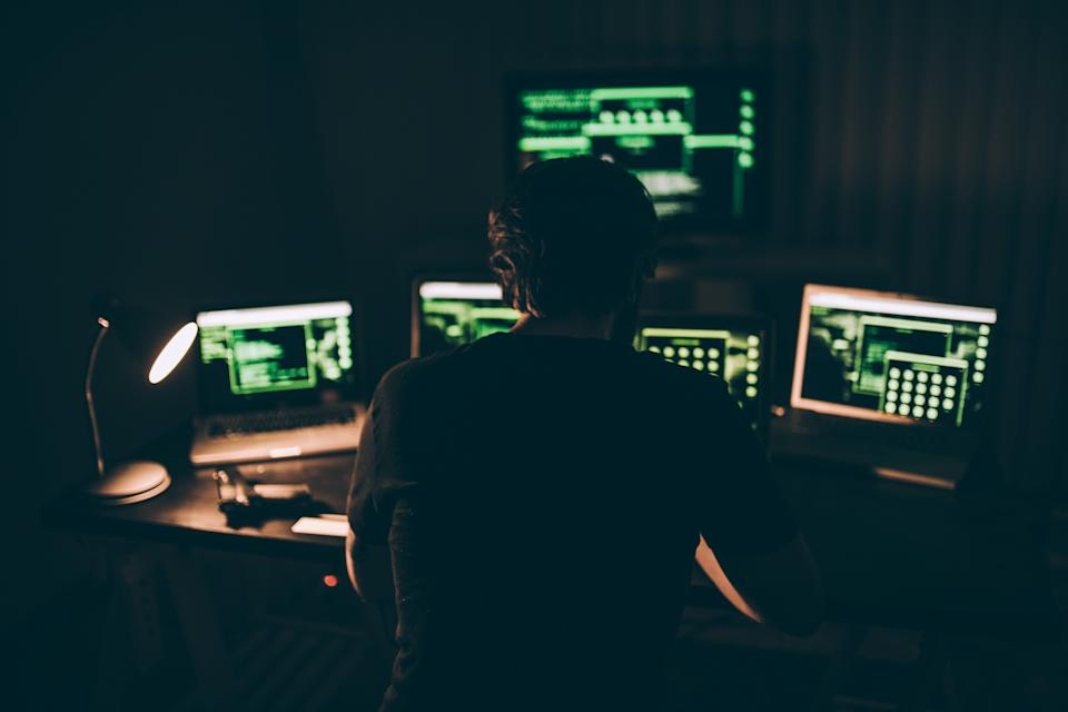 A hacker sitting in a dark room in front of lit computer screens