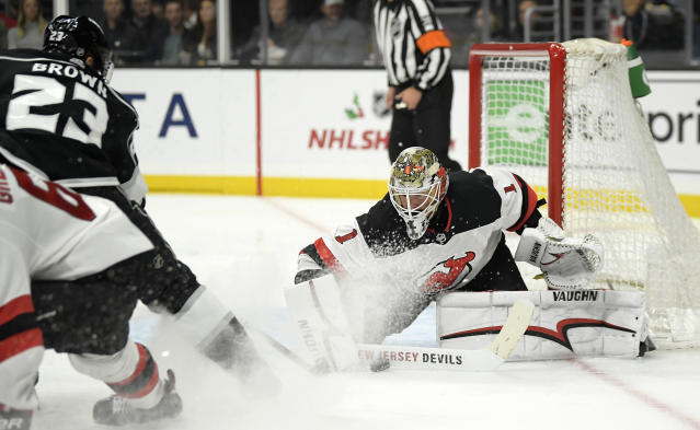 Los Angeles Kings right wing Dustin Brown, left, tries to get a shot past New Jersey Devils goaltender Keith Kinkaid during the second period of an NHL hockey game Thursday, Dec. 6, 2018, in Los Angeles. (AP Photo/Mark J. Terrill)